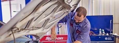 Auto Mechanic working under hood of a car